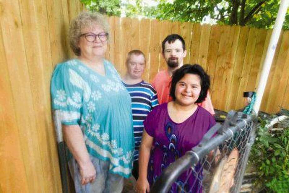 Debi Holley is seen with her adult children, Gabi, Jonathan and Andy, Thursday. All three of Holley's children have special needs, and with only a short chain-linked fence the family was in need of a more secure fence for their safety. Gracepoint Homes built the Holley family a wooden fence to keep Jonathan from leaving unexpectedly. Photo: Jason Fochtman