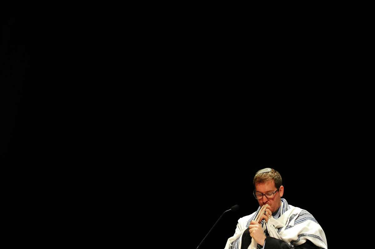Daniel Novick kisses his tallit during the Temple Sholom family Rosh Hashanah service in the auditorium of Greenwich High School in Greenwich, Conn. on Monday, Oct. 3, 2016.