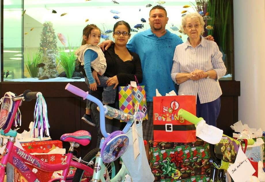 Joe and Esther Rodriguez, with three-year-old Joshua, and Gift Shop Team Leader Fran Wright of Memorial Hermann Southeast Hospital Volunteer Auxiliary.