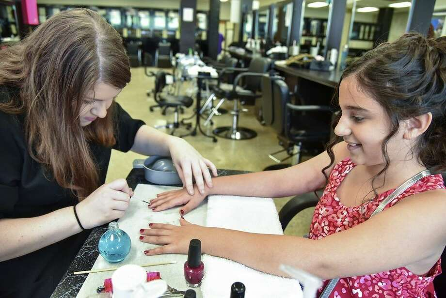 San Jacinto College cosmetology student Samantha Henderson, left, helped 9-year-old Cori Grissom to look her best for the Daddy-Daughter Dance. Photo credit: Rob Vanya, San Jacinto College marketing, public relations, and government affairs department.