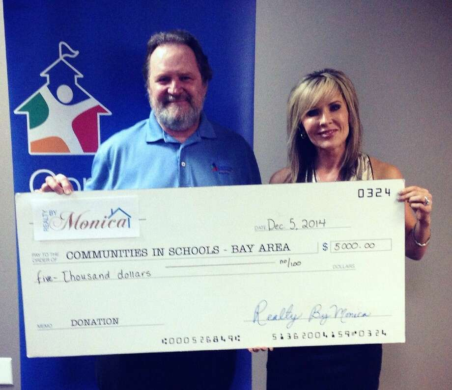 Monica Foster (right) of Realty By Monica presents her check to be a Gold Sponsor of the Keep Kids in Schools Golf Tournament to Peter Wuenschel, executive director of Communities In Schools-Bay Area, benefactor of the tournament.