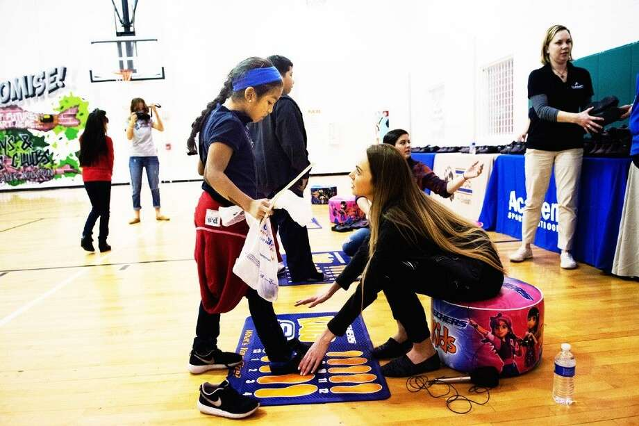 Country singer Danielle Bradbery helps kids get their correct shoe fitting during the BOBS from SKECHERS and Academy Sports + Outdoors event at John & Cissy Havard Boys & Girls Club on Monday, Dec. 14. Photo: Tony Gaines
