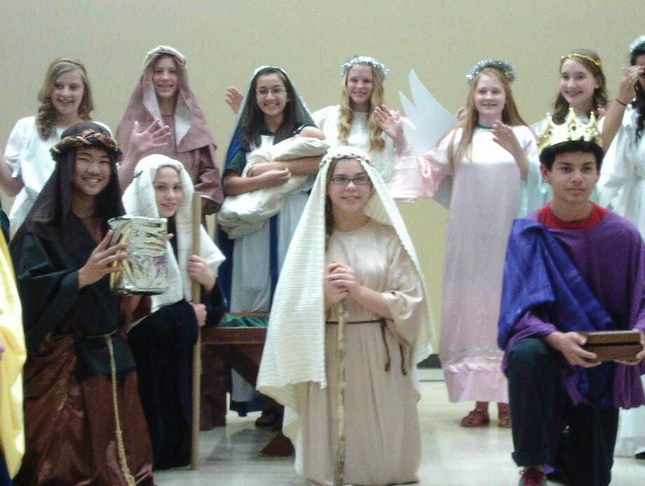 Holy Rosary School's eighth grade class traditionally presents the Nativity scene at the end of the Christmas pageant. Pictured are students who brought the manger scene to life.