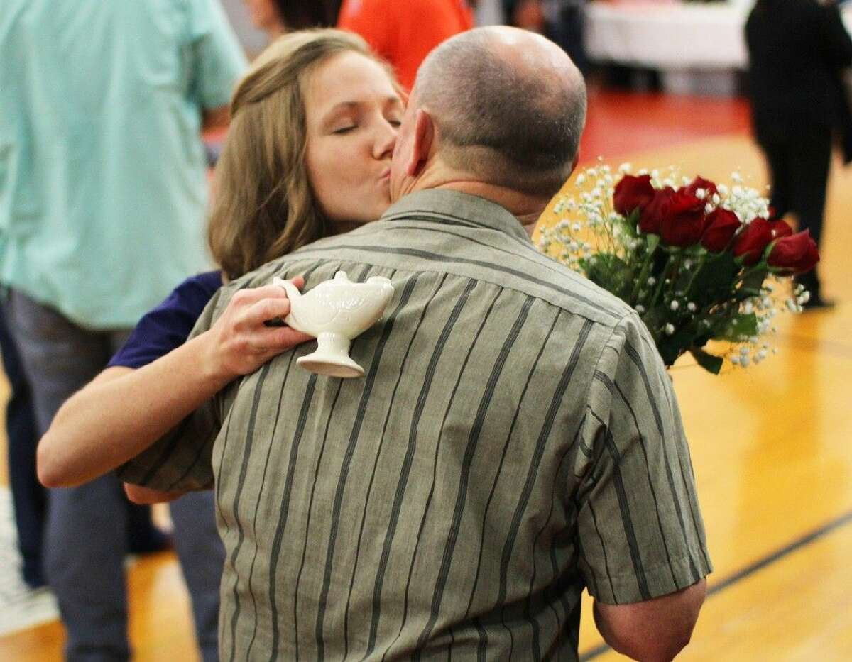 ACC Nursing student Jessica Colbert, of Danbury, left, kisses her father Bruce Colbert on the cheek after the Nurse Pinning ceremony on December 12.