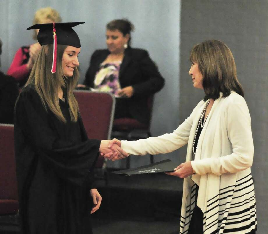 ACC Dean of Continuing Education and Workforce Development Dr. Patricia Hertenberger, right, presents student Brittany Bartolf, of Pearland, with her GED diploma during a graduation ceremony on December 9.