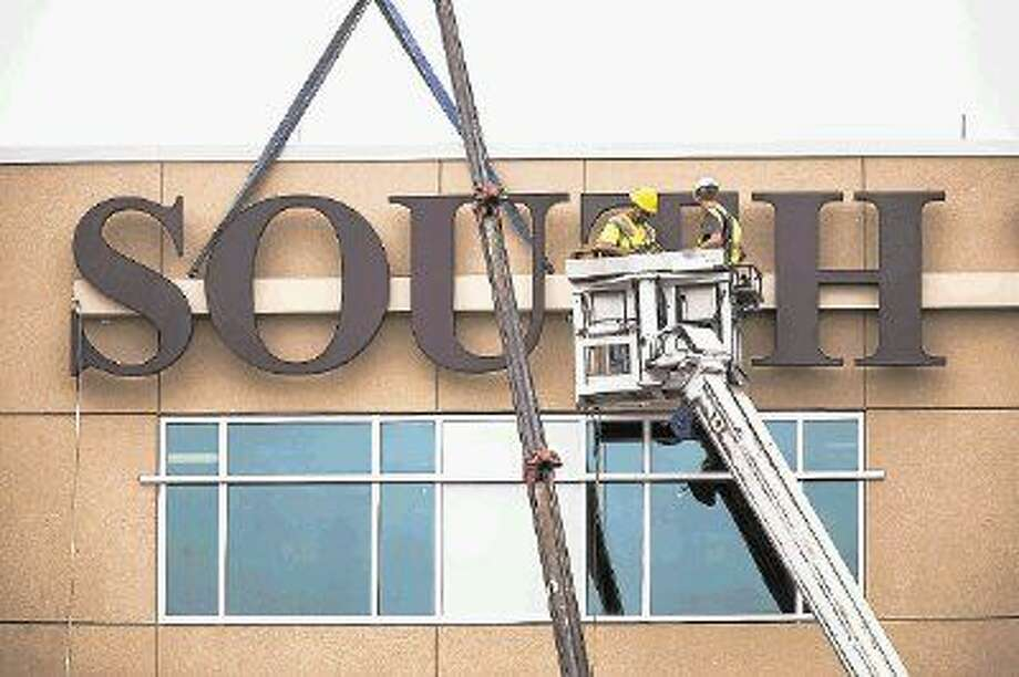 Construction workers install a new sign April 3, 2014, at Kingwood Medical Center. Photo: ANDREW BUCKLEY
