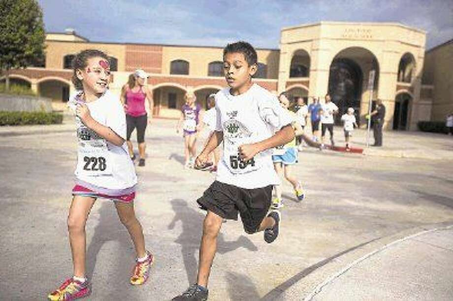 Elaine Andrew, left, and Josiah Trujillo compete in the Children's Race during Mothers Against Cancer's Virginia Gandy 5K Run and Walk on Sept. 27, 2014, at Kingwood High School. Photo: ANDREW BUCKLEY