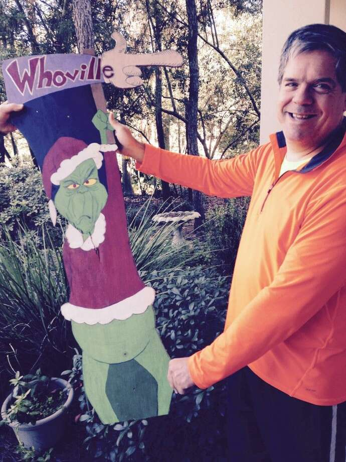 John Miller holds up the Grinch he created to point the way to his neighborhood's Whoville. However, the sign had to be replaced after it was damaged. Several other decorations in the area have been damaged or stolen.