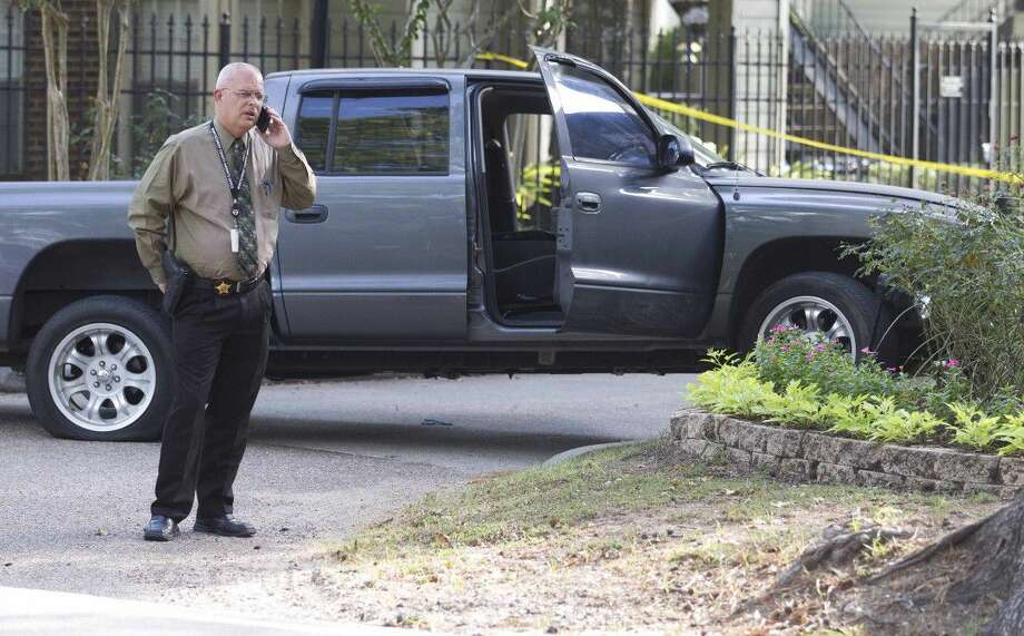 Law enforcement officers work the scene where two armed robbery suspects fleeing police crashed a vehicle at the Woodwind Village apartments Thursday in Spring. Officials found the suspects, with the help of a K-9 unit, on Oak Ridge Drive shortly after.