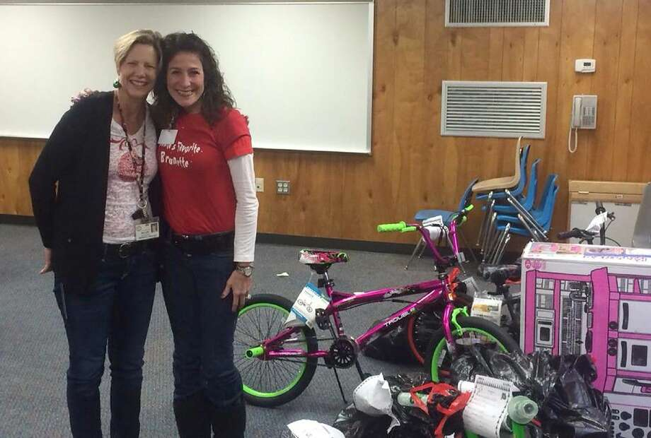 """Swenke Elementary School principal Liz Miller, left, and Lieder Elementary School principal Dr. Karen Stockton stand beside some of the gifts donated by the Swenke community to Lieder families in their third annual """"adoption."""" Photo: Submitted Photo"""