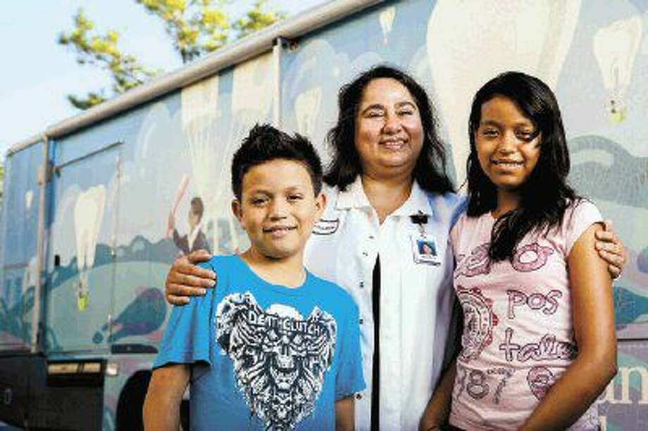 Memorial Hermann's Dr. Mahasti Chalajour (left) stands with two students in front of one of three Memorial Hermann Community Benefit Corporation Mobile Dental Vans. The program was recognized by the American Hospital Association as a NOVA Award winner for its efforts to improve community health. Memorial Hermann Earns American Hospital Association Awards for Commitment to Quality, Innovation in Palliative Care and Improving Community Health. Photo: James LaCombe