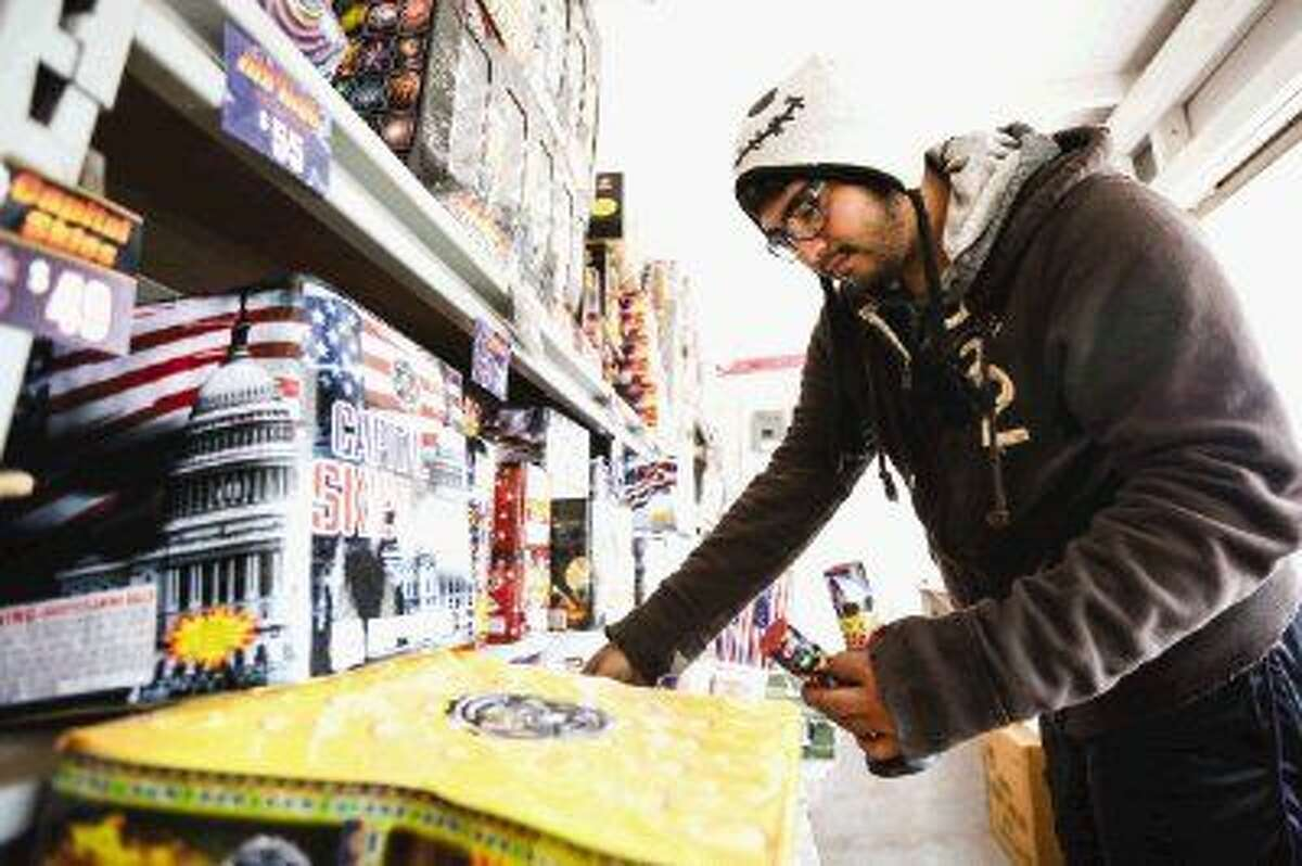 Fireworks stand manager Victor Fernandez organizes fireworks during a lull in customers on Monday off of FM 1488.