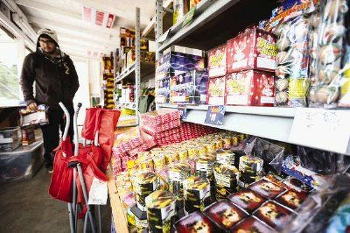 Fireworks stand manager Victor Fernandez organizes fireworks during a lull in customers on Monday off of FM 1488. Safety and property damage are the two main concerns for the county's fire departments, who have stated the purchase and use of fireworks in unincorporated areas is legal, but not within city limits.