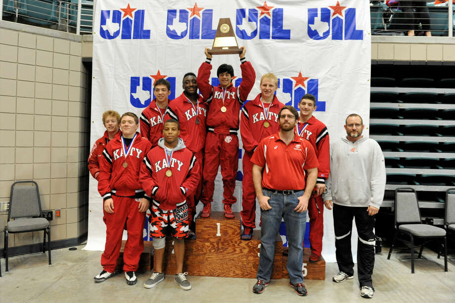 The Katy boys wrestling team celebrates with the Region 3-6A Tournament championship trophy, Feb. 13 at the Leonard Merrell Center in Katy. Photo: Craig Moseley
