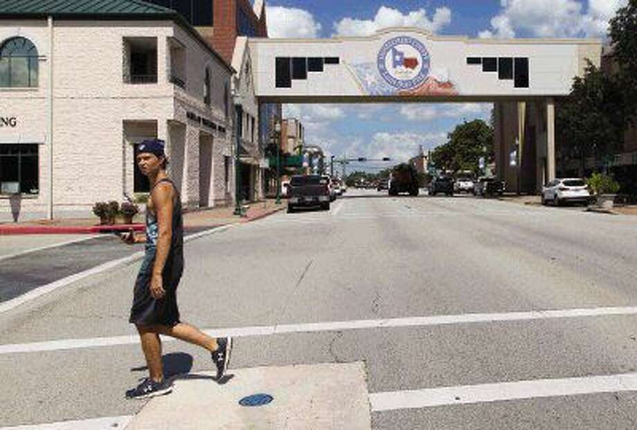 Levi Coplin walks across West Phillips Street as he searches for Pokemon in downtown Conroe Tuesday. Photo: Jason Fochtman