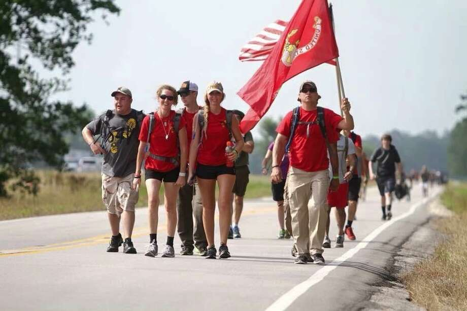 Steps 4 Vets Founder Will Rollins holds the Marine Corps flag at mile 10 of 22 during the 2015 Hero's Highway ruck march from Willis to Huntsville to raise awareness about the number of military veterans who commit suicide per day.