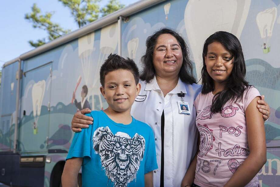 Memorial Hermann's Dr. Mahasti Chalajour stands with two students in front of one of three Memorial Hermann Community Benefit Corporation Mobile Dental Vans. The program was recognized by the American Hospital Association as a NOVA Award winner for its efforts to improve community health. Photo: James LaCombe