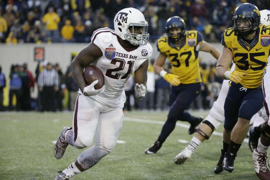 Texas A&M running back Tra Carson, left, runs against West Virginia in the second half of the Liberty Bowl. Texas A&M won 45-37.