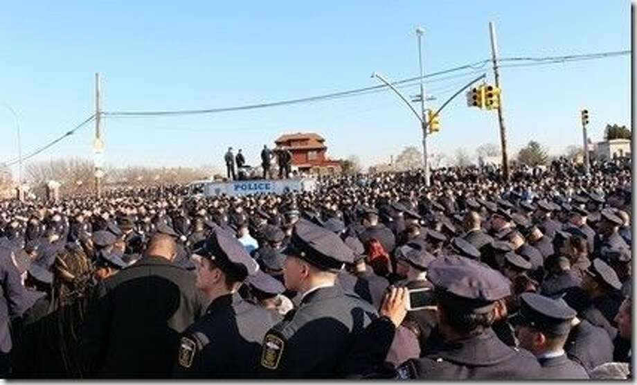 "Law enforcement from across the nation gathered Saturday, Dec. 27 in New York to honor fallen New York City Police Officer Rafael ""Ralph"" Ramos, who was shot to death Dec. 20 as he sat in his patrol car in Brooklyn a week earlier, along with his partner Officer Wenjian Liu."