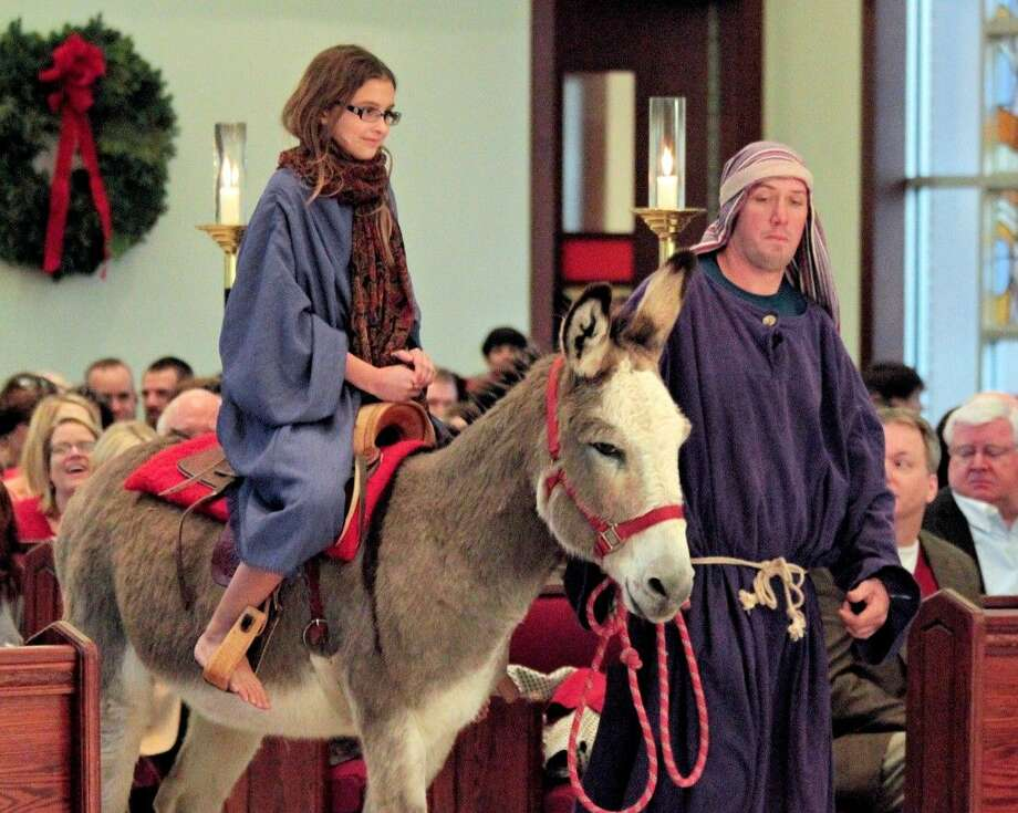 Elizabeth Hilgert, playing the young Mary, rides on a donkey with Joseph by her and accompanied by several herdsmen in the St. Francis Christmas pageant.