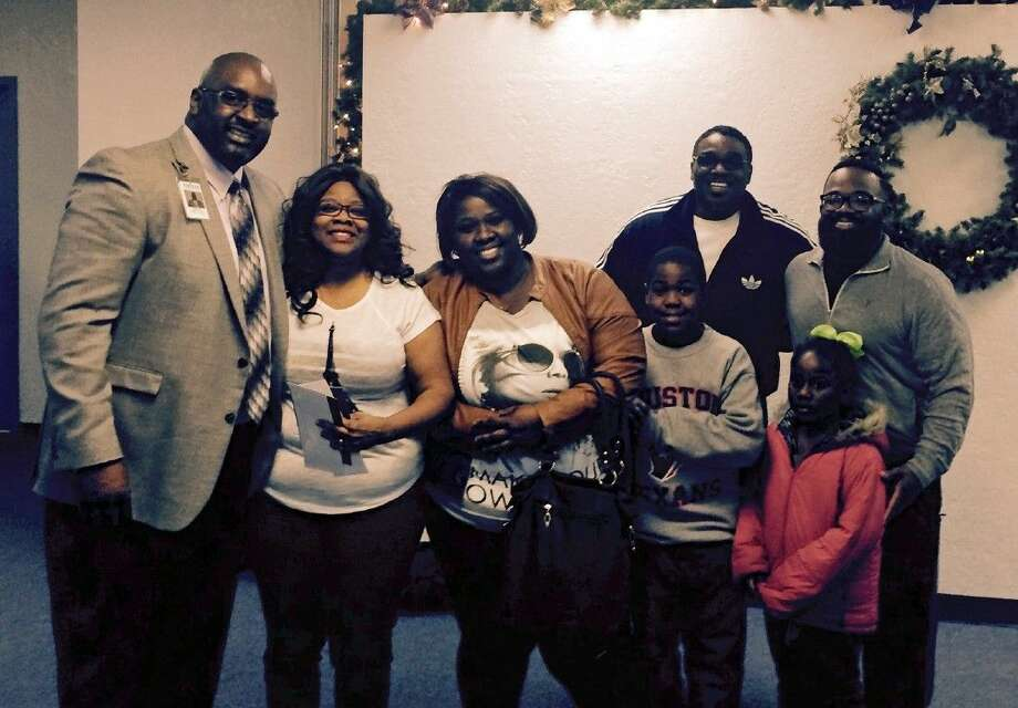 Cenikor Houston Facility Director Eugene Hall, on left, poses with Tessa Square and her children, Kenneth Thorns, far right, and Lady Gail and Pastor Johnson of Pleasant Hill Church of Deliverance. Tessa Square's family and Kenneth Thorn's family received checks for more than $600 to assist them during the holiday season.