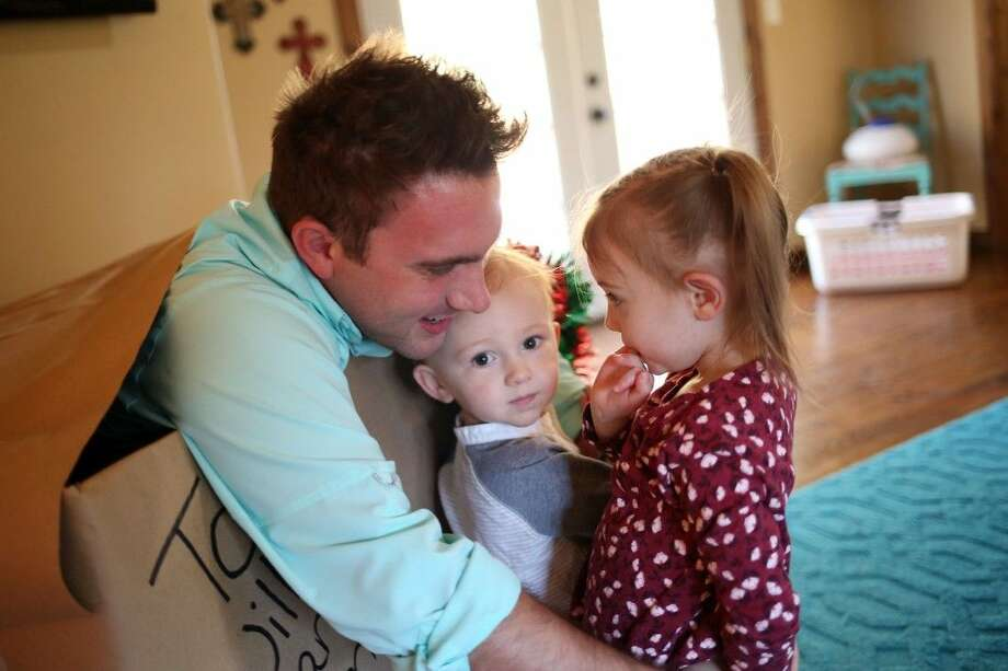 Petty Officer Second Class Ryan Dodd embraces his children, Willow and Liam, after a surprise reunion on Friday. Photo: Victoria Good