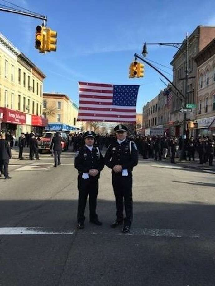 Pearland Police Officers Rivera and Thedford stand in front of an American flag and the throng of people who came to New York City to pay last respects to fallen Officer Ramos.