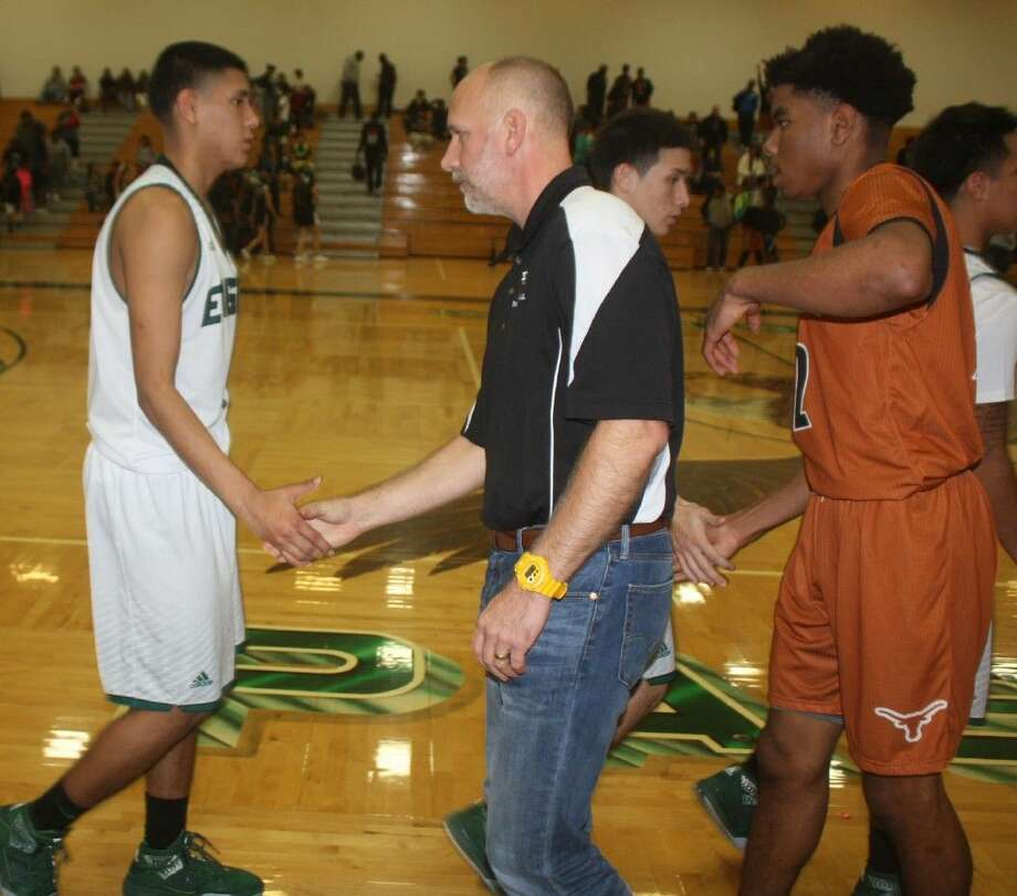 Dobie head coach Kevin Cross and his players shake hands with the Eagles, following the team's narrow 22-6A win Friday night. Photo: Robert Avery