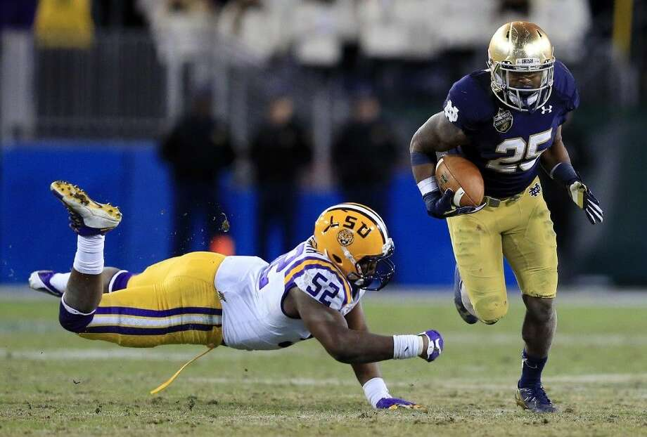 Notre Dame running back Tarean Folston, right, gets past LSU linebacker Kendell Beckwith in the second half of the Music City Bowl. Notre Dame won 31-28.