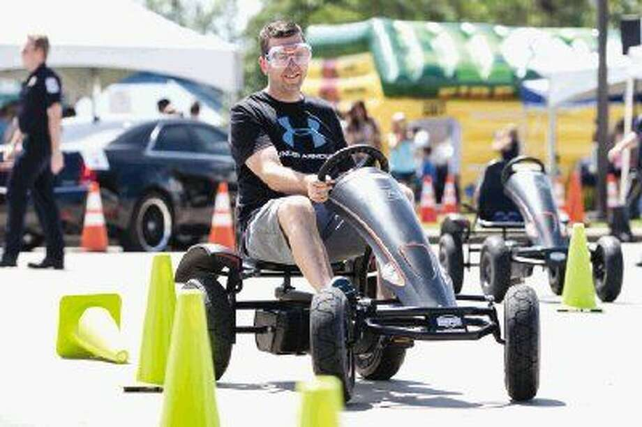 The Woodlands resident Adam Watson runs over a cone while using equipment with the Cruise with Caution program during the National Night Out Community Safety Expo on Sept. 19 at Northshore Park. Photo: Michael Minasi