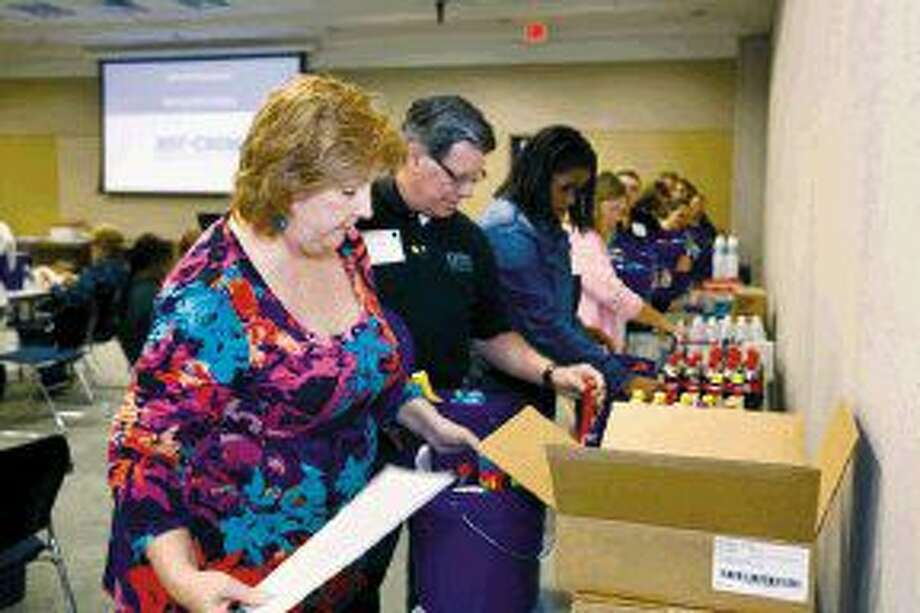 Humble ISD Creekwood Middle School teachers Kim Delacruz and Paul Tagliabue gather products produced at area chemical plant manufacturing, including Coke bottles and Gorilla Gel.