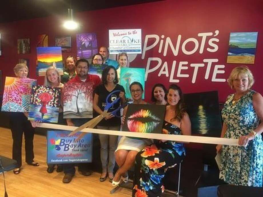 Members of the Clear Lake Chamber of Commerce stand by as owner Maggie Young cuts the ribbon to dedicate the opening of Pinots Palette located at 1020 W. Nasa Parkway in the Point Nasa Shopping Center during a ceremony Tuesday, July 12.