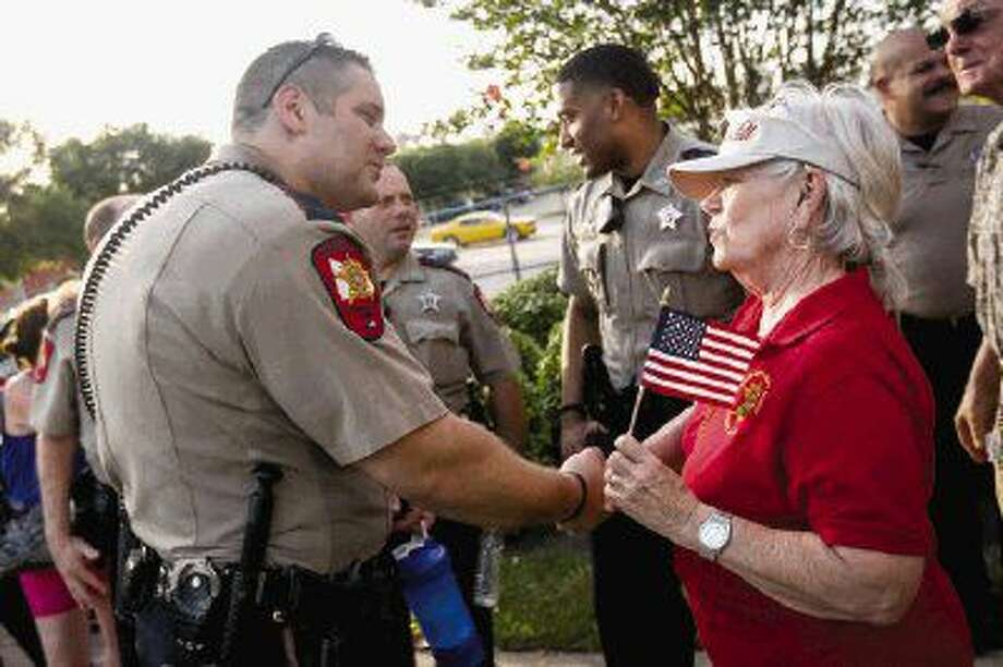 Stella Gordon, a resident in Montgomery County, shakes hands with Deputy Dustin Savage, of the Montgomery County Sheriff's Office, during the prayer vigil for law enforcement hosted by the Montgomery County Sheriff Citizen Academy Alumni on Saturday at the Criminal Justice Center in Conroe. Photo: Michael Minasi