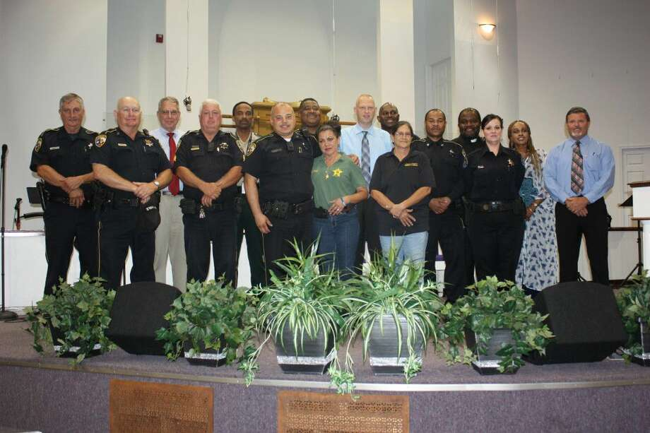 Law enforcement officers representing Cleveland Police Department, Liberty County Sheriff's Office, Polk County Sheriff's Office and Pct. 6 Constable's Office are joined by Pastor Gary Driver, and wife, Shere, of C. C. Driver Revival Center, on Thursday, July 14, for a unity service between police and the black community in Cleveland.