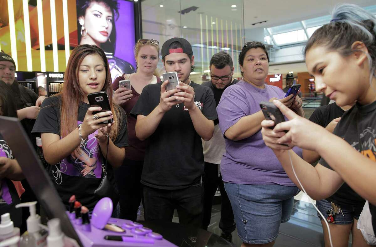 A shoppers take photos of MAC's Selena Collection at the Galleria on Thursday, Oct. 6, 2016, in Houston. Stores were expecting to sell-out this morning.