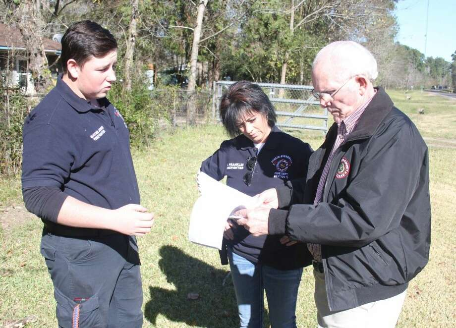 Punkin-Evergreen Volunteer Department Lieutenant Shayne Jones (left) and firefighter Scooter Franklin (middle) present the blueprints of the fire station they hope to build to Pct. 3 Commissioner Thomas Bonds (right). Photo: Jacob McAdams
