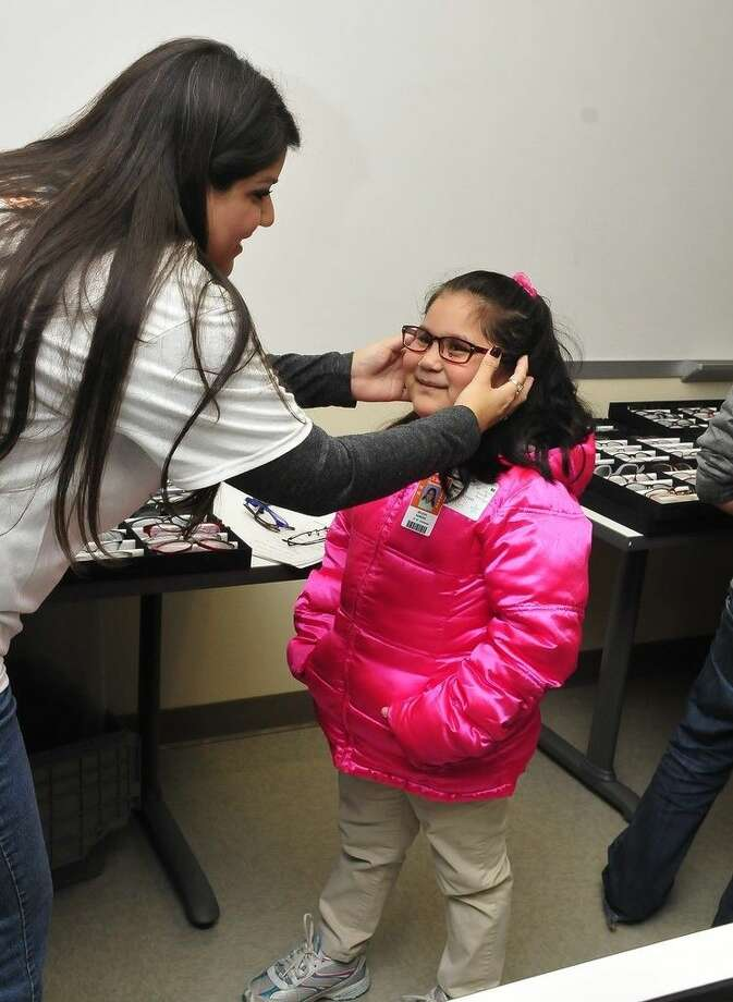 Yvonne Steiner, Walmart vision center manager, assists Selena Romero, Pasadena Independent School District student, with the fitting of new eyeglass frames at the December 2015 See to Succeed event at San Jacinto College. Photo credit: Jeannie Peng-Armao, San Jacinto College marketing, public relations, and government affairs department.