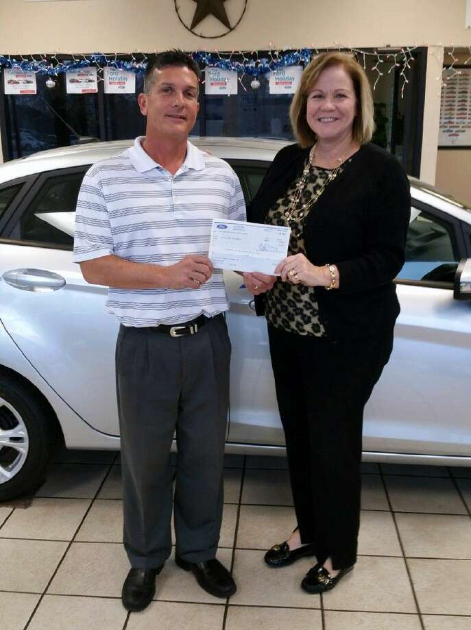 Robert Dunn, co-owner of BJ Ford in Liberty, presents a $1,000 check to Debbie Dugger, executive director for CASA Liberty-Chambers Counties. Photo: Submitted