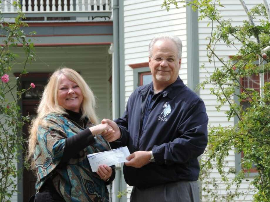 Candace Jones, director of George Ranch Historical Park, accepts WCA Waste management's 30,000 donation for the Park's Title One school field trip program with a handshake from Jerry Martin, WCA Region 2 vice president. Photo: Submitted Photo