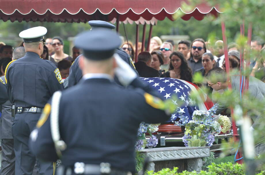 Officers salute the American flag-covered casket of fallen Bellaire police officer Anthony Marco Zarate at his burial Monday.  Photo: By Jay R. Jordan
