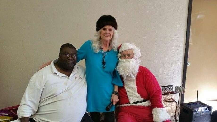 "Albert Thomas, vice-president of Men Who Set Trends along members of the community Diane Holland and ""Santa"" at the MWST first timeChrismas gift giveaway."