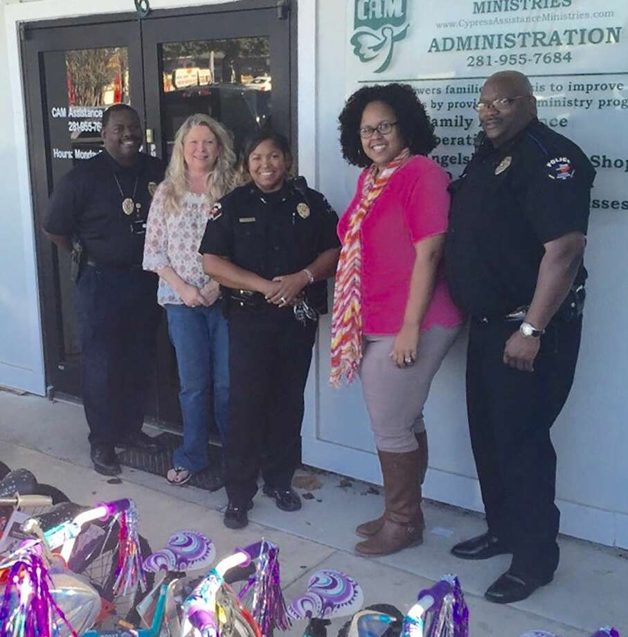 Representatives from the CFISD police department, including Sgt. Cedric Nolly, far left; Officer Tamesa Singleton, third from left; and Officer Burl Johnson, far right; delivered bicycles to Cypress Assistance Ministries on Dec. 17.