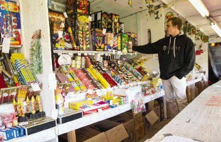 Kolby Morrow points out some of the typical high-selling items at a fireworks stand off Texas 242 on Tuesday in Conroe.