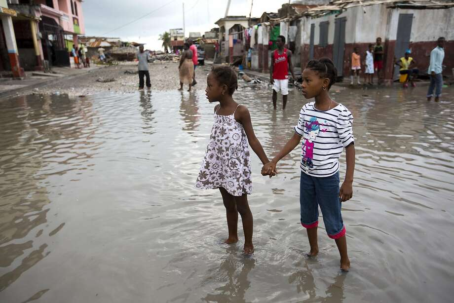 Girls hold hands as they help each other wade through a flooded street in the city of Les Cayes, Haiti. Photo: Dieu Nalio Chery, Associated Press