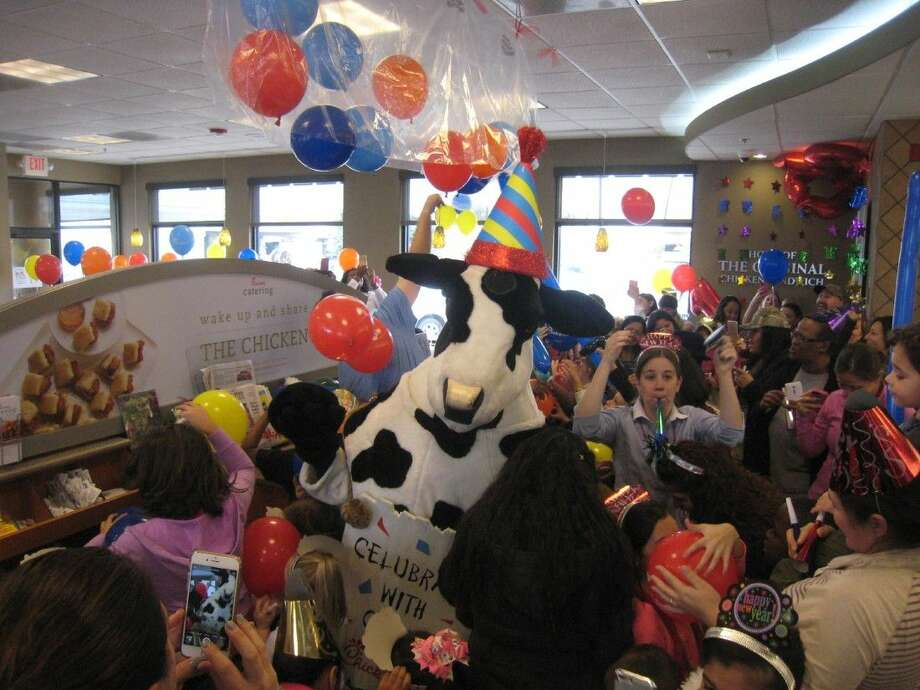 Guests cheer as the balloons drop during the Noon Year's Eve party at Chick-fil-A in Fall Creek Thursday, Dec. 31, 2015.
