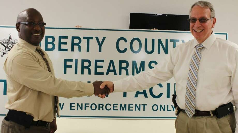 Warden Robert Lacy with Corrections Corporation of America presents a new sign for the Liberty County Sheriff's Office firing range to Sheriff Bobby Rader (right). Photo: Submitted