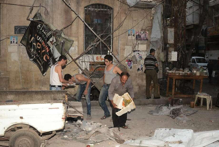 Aleppo residents inspect the damage caused by an artillery attack in thegovernment-controlled side of the northern city following fighting between government forces and rebels. Photo: GEORGES OURFALIAN, AFP/Getty Images