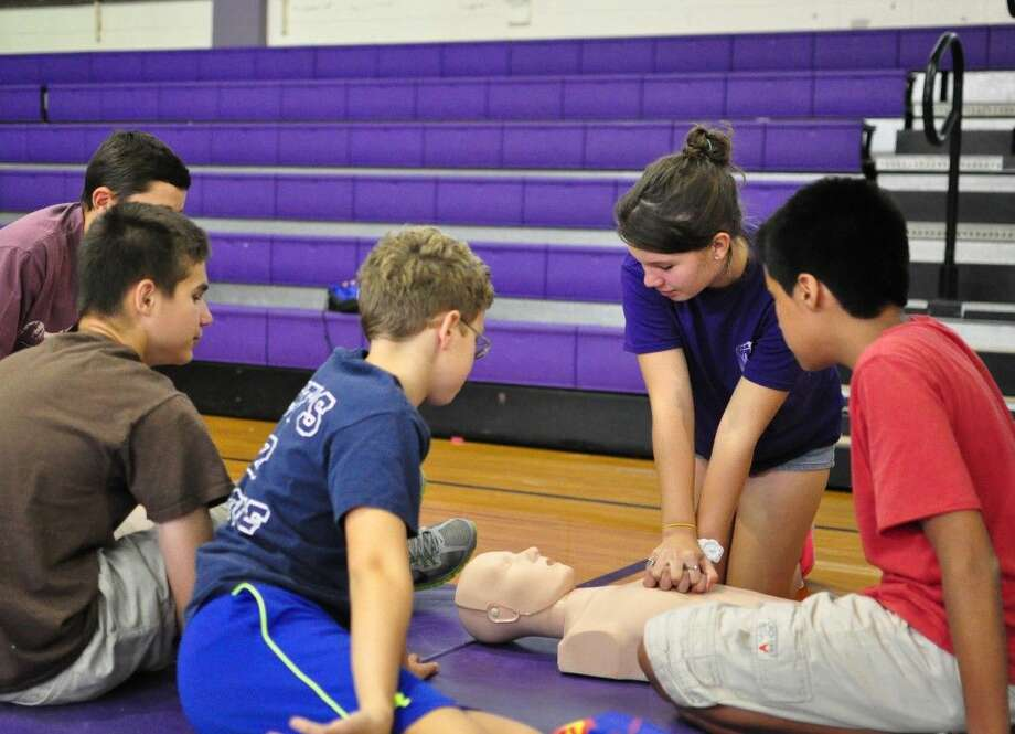 Students take turns practicing CPR on 'smart dummies' that flash a green light when the technique is properly done.