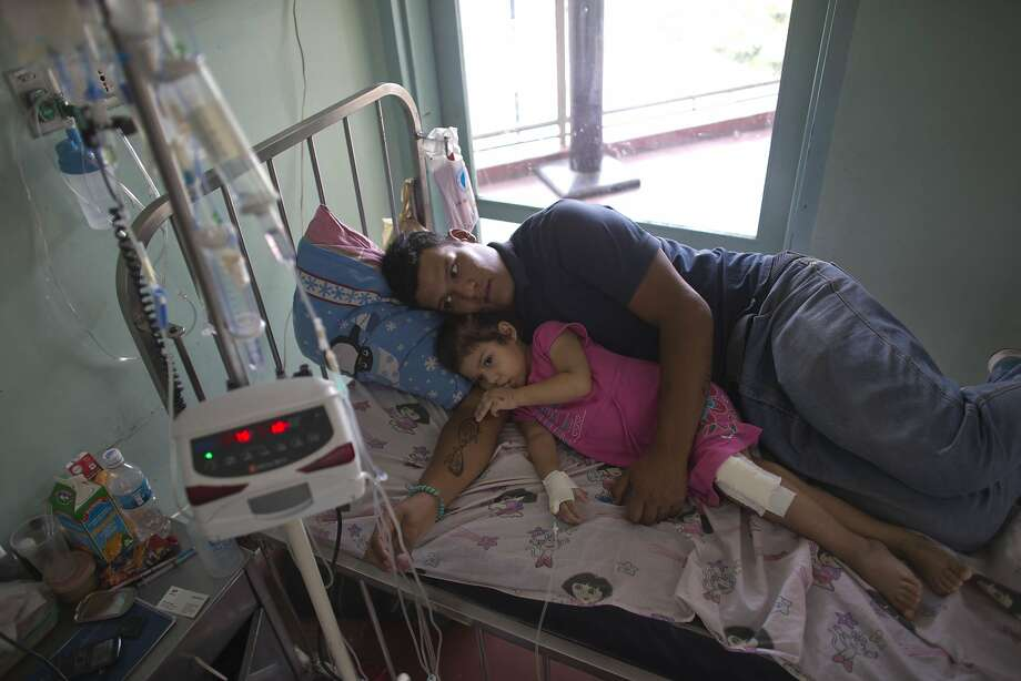 Maykol Pacheco curls up with his daughter, Ashley, during her two-month stay in a Caracas hospital. President Nicolas Maduro calls the medical crisis an invention peddled by his political opponents. Photo: Ariana Cubillos, Associated Press