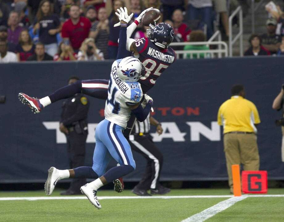Houston Texans wide receiver Nate Washington hauls in a 42-yard pass for a touchdown as Tennessee Titans cornerback Coty Sensabaugh defends in the second half. The Texans won 20-6.